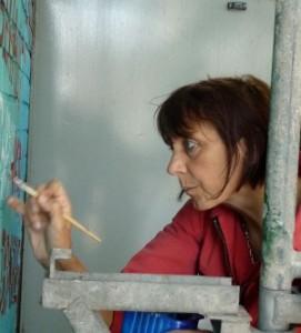 """Malerin der FrauenFreiluftGalerie bei der Arbeit am 13. Wandgemälde """"Immer an der Wand lang - Frauengemälde am Hafen"""""""